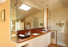 Designer bathroom - fitted washstand with white base units, large mirror and glass shower cubicle
