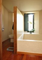 Bathtub below window with partition screening toilet