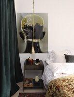 Metal bedside table below large artwork