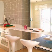 Kitchen counter with protruding breakfast bar and white bar stools in front of glass panels looking into living room
