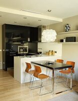 Designer pendant lamp above table and retro shell chairs next to white, monolithic counter in open-plan kitchen