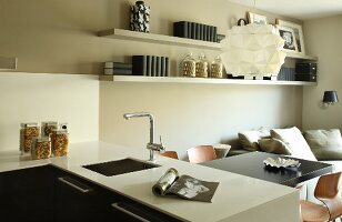 View across white counter with fitted sink in front of dining area below designer pendant lamp in open-plan interior