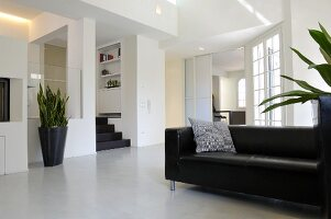 Black leather couch in open-plan interior with minimalist ambiance; black planter on floor in front of raised platform