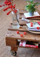Branch of red berries in vase and red dice on coffee table made from wooden pallet and castors
