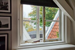 Lattice window with brass fittings in gable wall of attic room; view of roofs and trees