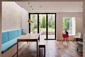 Modern table with matching bench, masonry bench with blue cushions and classic chair next to terrace doors with garden view