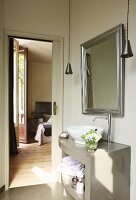 Curved, grey washstand with basin below framed mirror on wall with bedroom seen through open door in background