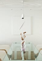 Branch of cotton bolls in sand-filled vases on designer glass table, classic chair and modern, white artwork on wall