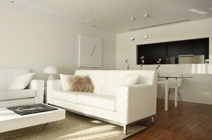 White designer furniture in open-plan interior with dining area next to kitchen pass-through