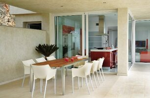 Dining set with plastic shell chairs on terrace of modern holiday home