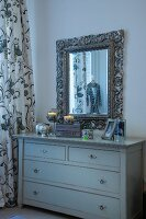Simple, pale grey chest of drawers below mirror with carved frame