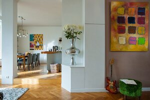 Modern artwork on grey-painted wall next to open doorway with view of dining area in background