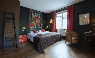 Colourful Oriental painting above bed and red suitcases used as bedside table in bedroom painted dark brown