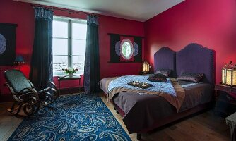 Double bed with purple headboard, rocking chair and paisley rug in bedroom with red walls