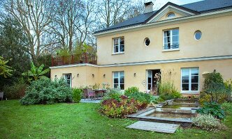 Back façade of French country house with terrace and ponds