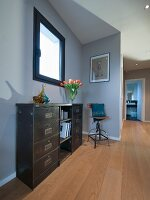 Industrial-style sideboard and metal chair in grey-painted hallway