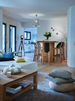 View past coffee table and floor cushions to wooden table and bar stools in dining area