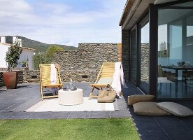 Bamboo lounger and woven rug on terrace next to glass facade of Spanish holiday home