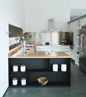 Elegant fitted kitchen with U-shaped counter decorated with pots and olive-wood bowl in purist style