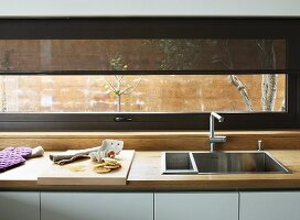 Square, stainless steel sink in kitchen counter with wooden worksurface below ribbon window with translucent roller blind