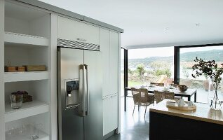 Stainless steel, side-by-side fridge freezer flanked by kitchen cabinets and shelving; dining area in front of panoramic window in background