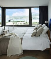 Double bed with bed linen in natural shades in bedroom with panoramic view through corner window