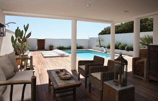 Rattan furniture on roofed terrace with pool in background