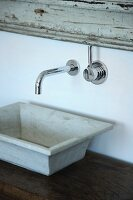Rustic stone sink on wooden table below designer, wall-mounted tap