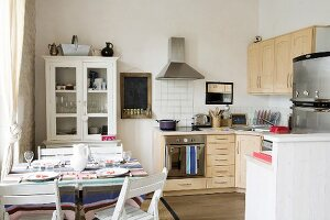 Set table in kitchen-dining room with wooden cabinets