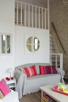Colourful scatter cushions and grey throw on sofa in front of gallery element with stairs to one side