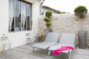 Modern loungers on terrace with wooden deck and stone wall