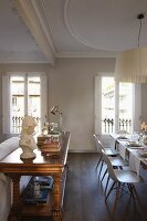 Bulky, antique console table, festively set dining table and classic chairs in period building with stucco ceiling