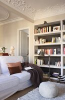 Seating area with bookcases, stucco ceiling, pouffe and white sofa