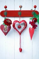 Red and white spotted heart ornament decorated with zinnia, dahlia and snap dragon hung on vintage coat rack
