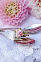 Rosebud on fork on white lace doily and pink dahlia flower in background