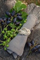 Linen napkin tied with jute cord in a figure-of-eight knot next to freshly picked grapes