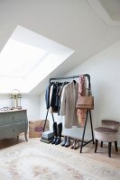 Antique chest of drawers, women's clothing on clothes rail and upholstered chair in bright attic room