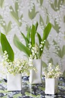 Lily of the valley in designer vases in front of wallpaper with lily of the valley pattern