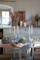 Wreath of cream polyantha roses and candlesticks on rustic table in country-style kitchen