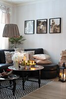 Christmas decorations on tray table, black leather sofa and photos on wall