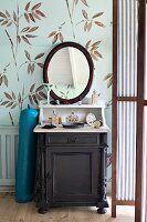 Dressing table with dark wooden base cabinet, pale top and oval mirror against leaf-patterned wallpaper