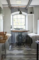 Tabletop on old sewing machine base and pale grey benches below window on platform with chequered floor