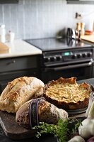 Various types of bread and quiche on counter