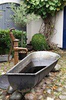 Vintage zinc bathtub next to pump in cobbled courtyard