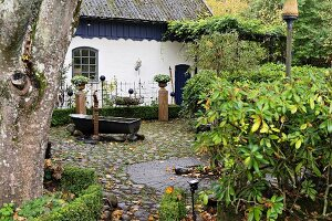 Vintage zinc bathtub on pebble-cobbled terrace in garden of white-painted country house