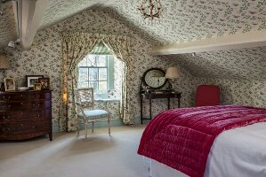 English-style attic bedroom with floral wallpaper on walls and ceiling and matching curtains