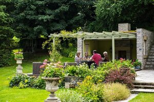 Group seated at table under pergola in summer garden