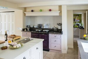 Island counter and classic cabinets with doors in various pale shades in open-plan kitchen