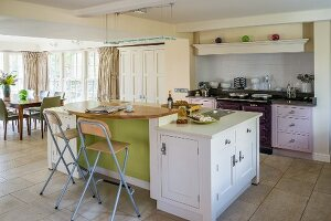 Island counter and classic cupboard doors in various colours in open-plan kitchen with dining area in background