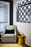 Reading armchair with graphic upholstery in corner next to retro side table and wall aperture filled with geometric window grate